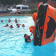 PST STUDENT DEMONSTRATING HOW TO TURN OVER THE LIFERAFT.